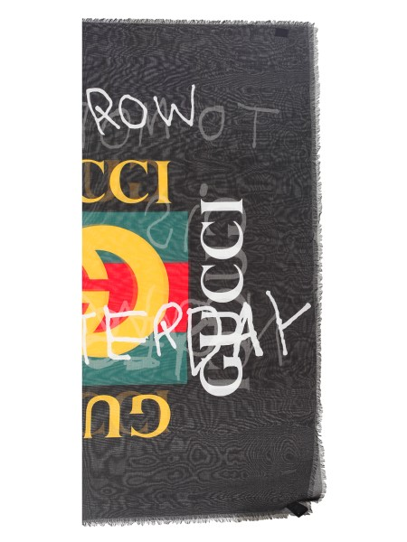 "Shop GUCCI  Stola: Gucci shawl in black modal and silk with Gucci vintage logo print and phrase ""tomorrow is now yesterday"" by Coco Capitán, a famous Spanish artist. Fringed edges. Dimensions: 140 cm x 140 cm. Composition: 85% modal and 15% silk. Made in Italy.. 494005 3G856 -1000"